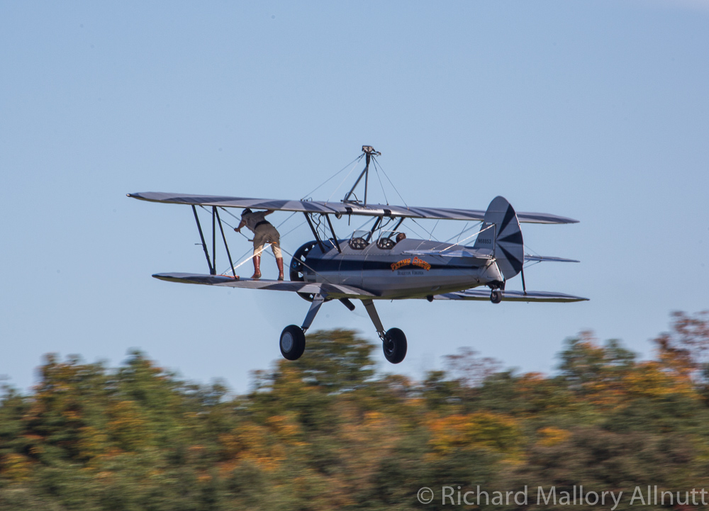 Wing walker Chuck Tippett climbs out onto the wing of the Stearman while Kirk Wicker flies her straight and level. (photo by Richard Mallory Allnutt)