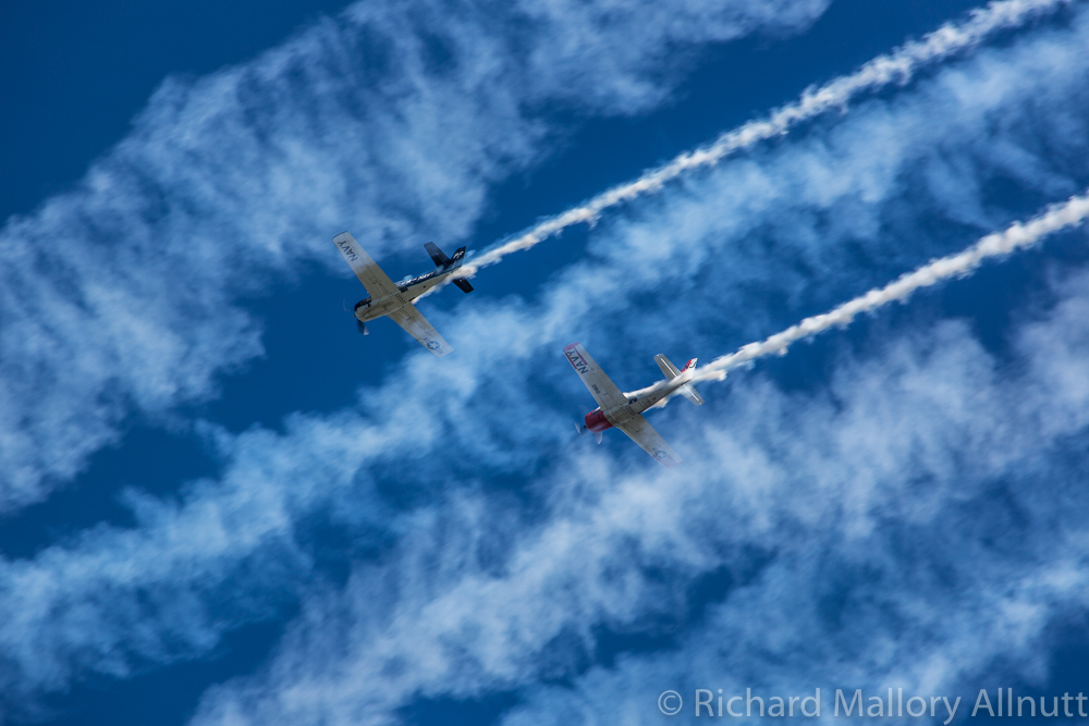 The Trojan pair flying through the cast-off smoke of the Texan flypast. (photo by Richard Mallory Allnutt)
