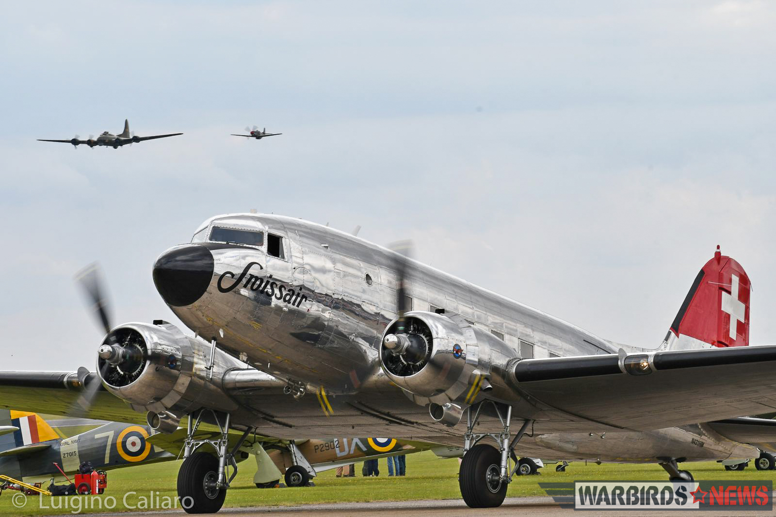 A fabulously maintained Swiss-based DC-3 taxies past a row of Hawker Hurricanes while B-17G 'Sally-B' flies overhead in company of a 'Little Friend'. (photo by Luigino Caliaro)