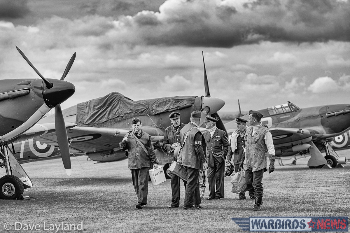 RAF re-enactors walk on the flight line near the Hawker Hurricanes. (photo by Dave Layland)