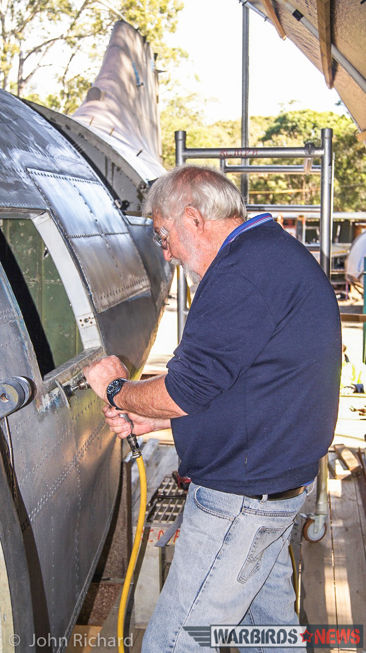 Volunteer Ray Fairall preparing for refitting of fuselage panelling, port side. (photo by John Richard)