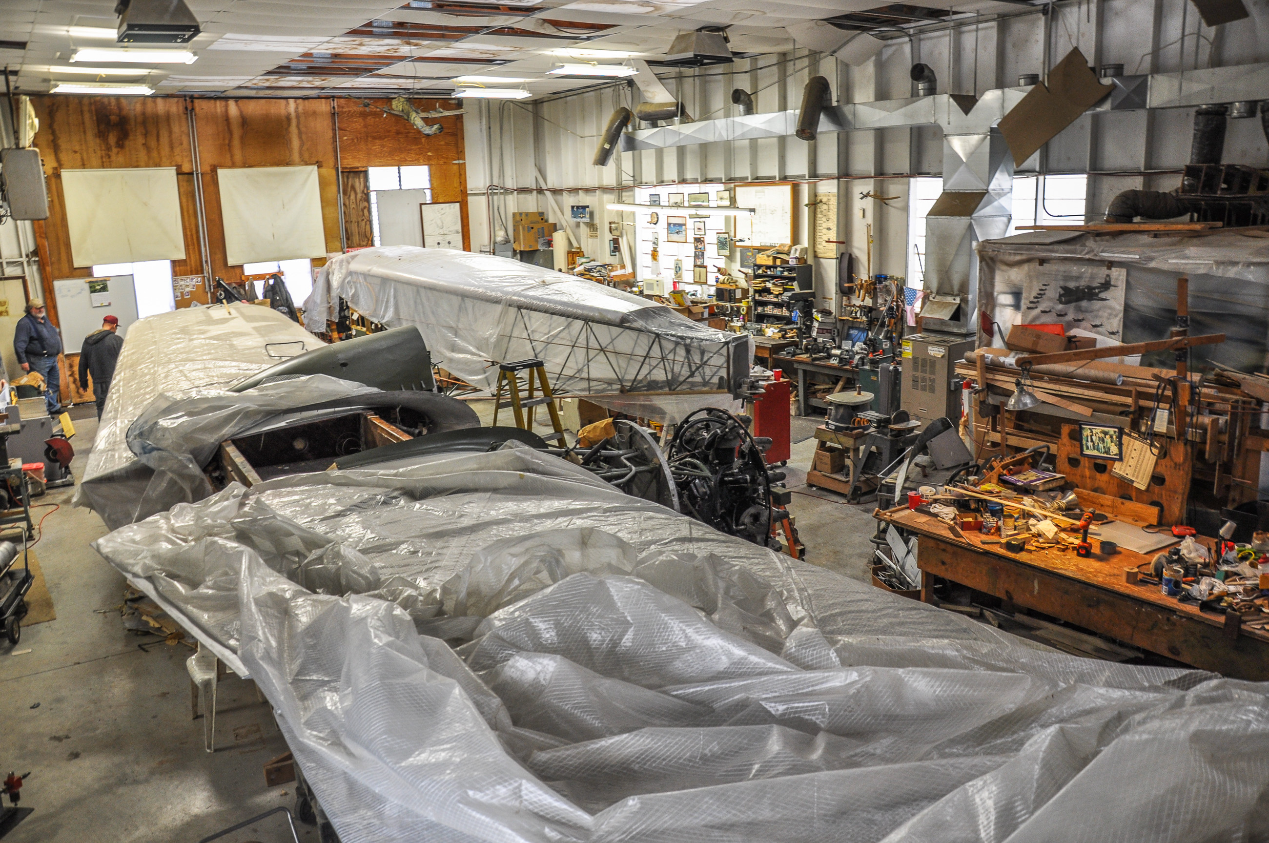 An image inside of the restoration shop.  The wings and fuselage are covered with plastic tarps in the event that the roof started to leak. (David Cohen photo)