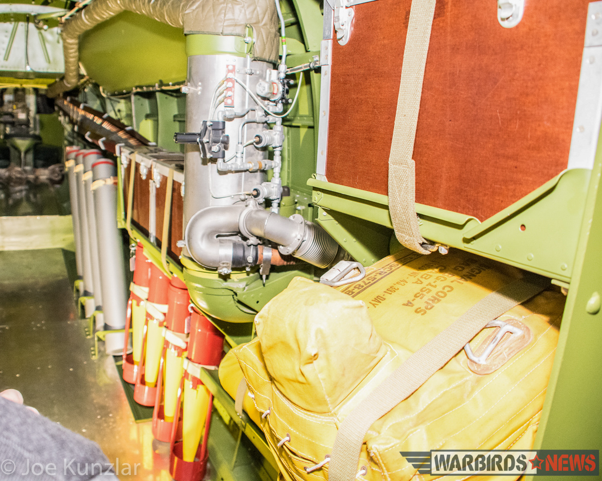 A view inside the rear fuselage where you can see the orange and yellow-painted flares, the yellow bulk of the stowed life raft, and the ruddy brown of the phenolic ammunition container. (photo by Joe Kunzlar)