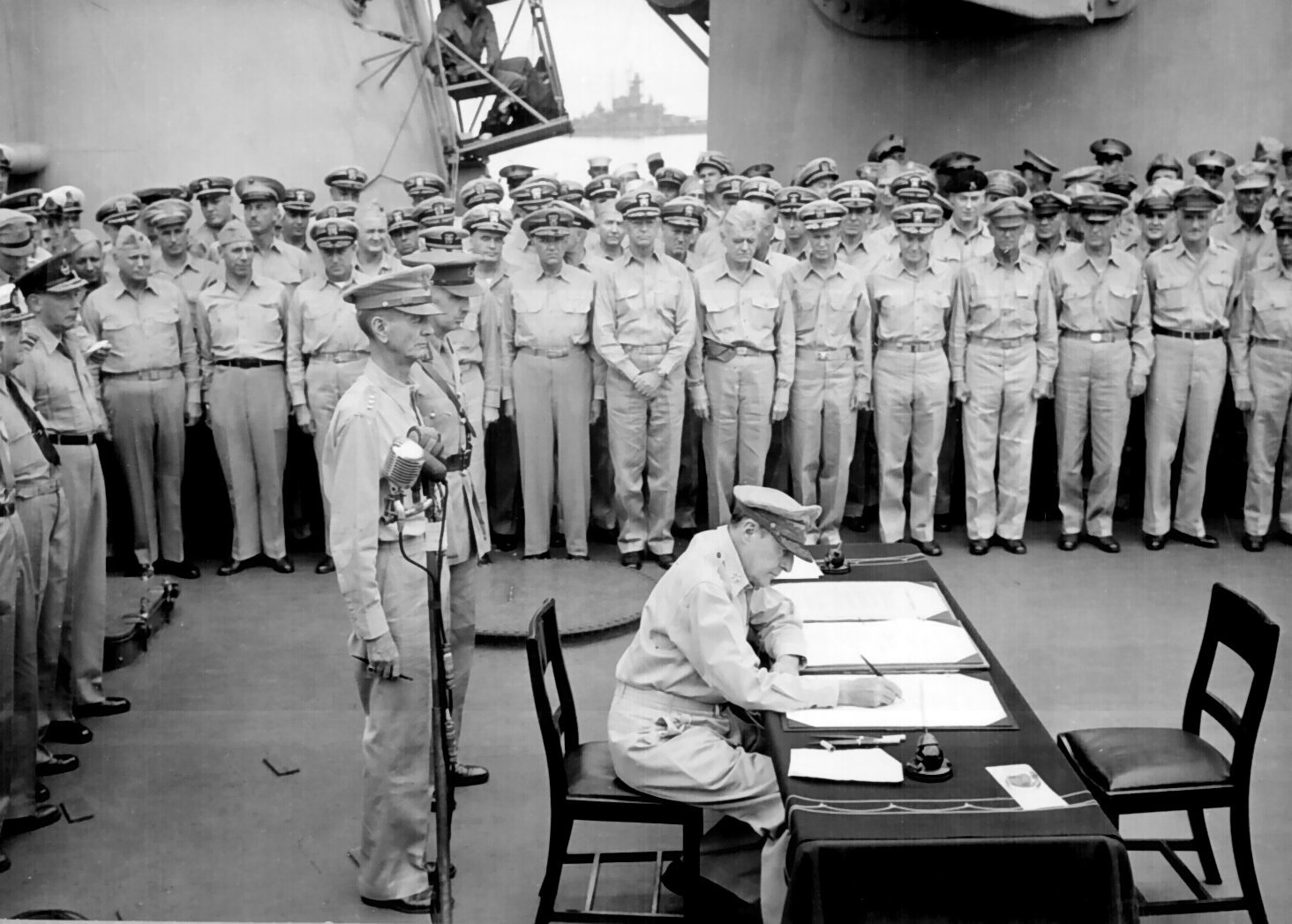 Douglas MacArthur signing the Japanese surrender documents aboard the USS Missouri on September 2nd, 1945. (photo via wikipedia)