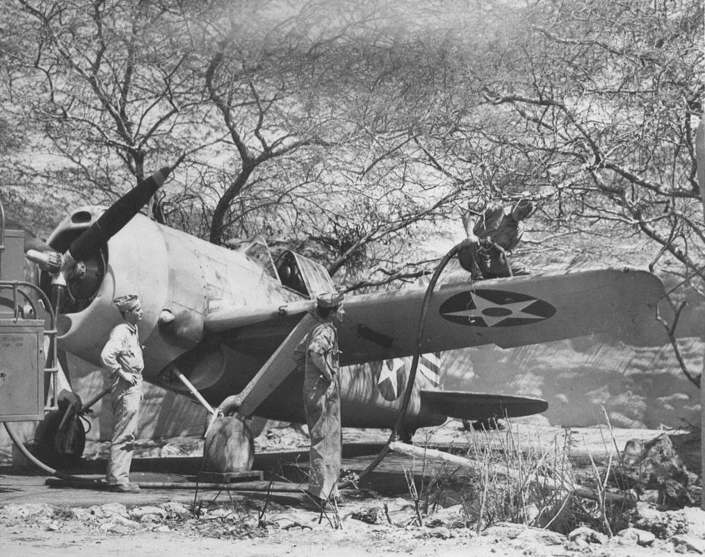 A Brewster F2A Buffalo being refueling at Ewa in May, 1942. Note the attempt to hide the aircraft under the thorny Kiawe trees and the sandbag revetment in the background.