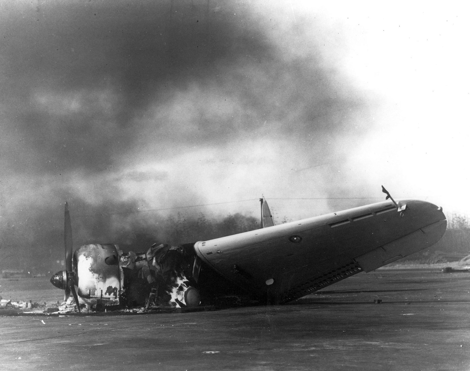 The remains of a Douglas SBD Dauntless dive-bomber burns on Ewa's ramp on Dec. 7, 1941.