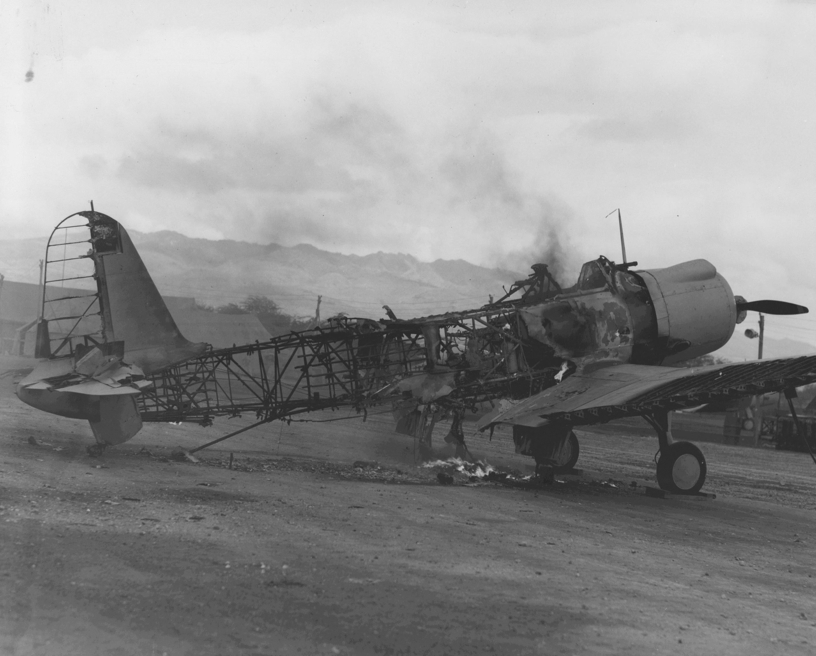 A Vought SB2U Vindicator dive-bomber, still smoldering, shortly after the Japanese attack on Ewa and Pearl Harbor.