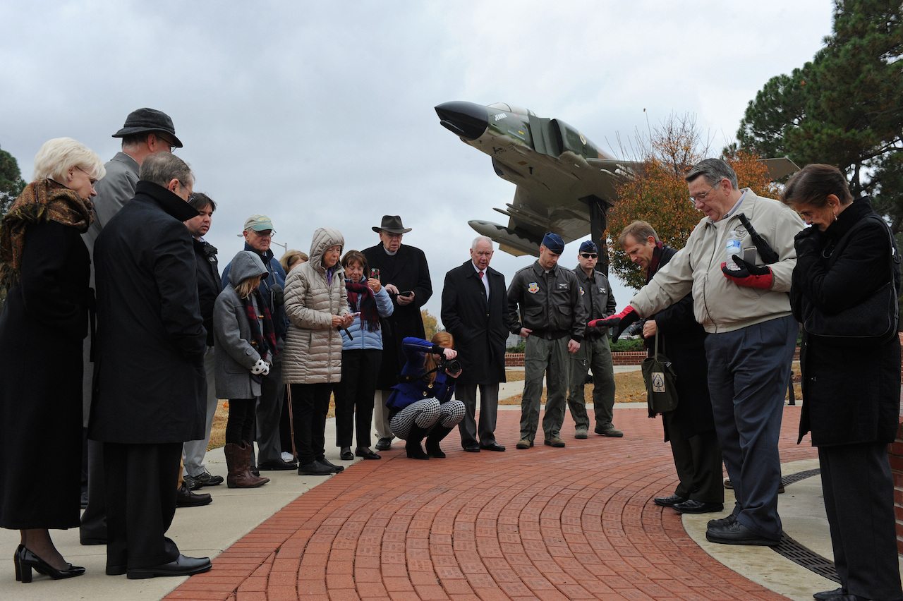 Family and friends of Capt. William Jarman Jr., an F-4 Phantom pilot with the 335th Tactical Fighter Squadron during the 1960s, who died in 1969 during an aircraft collision over Fort Bragg, N.C., gather in Heritage Park at Seymour Johnson Air Force Base, N.C., during a ceremony where two bricks were dedicated to Jarman's legacy, Nov. 14, 2014. The bricks are inscribed with his name and service details. Bricks surround the Heritage Park F-15E Strike Eagle memorial fountain, commemorating heroes from the base's past. Jarman's family and friends visited the base, Nov. 14, to connect with the Airmen of the 335th Fighter Squadron, a squadron Jarman dedicated his life to. (U.S. Air Force photo/Airman 1st Class Aaron Jenne)