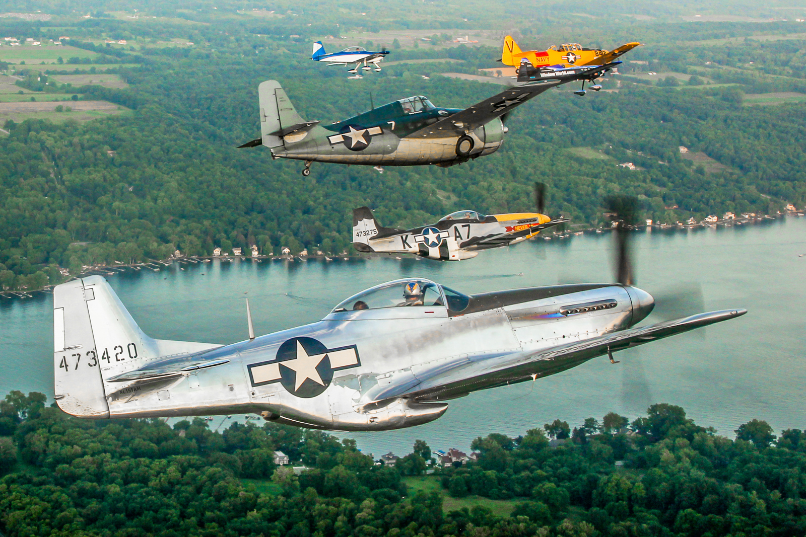 A mighty formation over the Genesee Valley featuring Andrew McKenna in his P-51D Mustang alongside Greg Shelton in the FM-2 Wildcat, Mark Murphy in another P-51D, Rob Holland in the MXS-RH, Jerry Kerby in the RV-8A and Dave Murphy in the Texan. (photo by Tom Pawlesh)