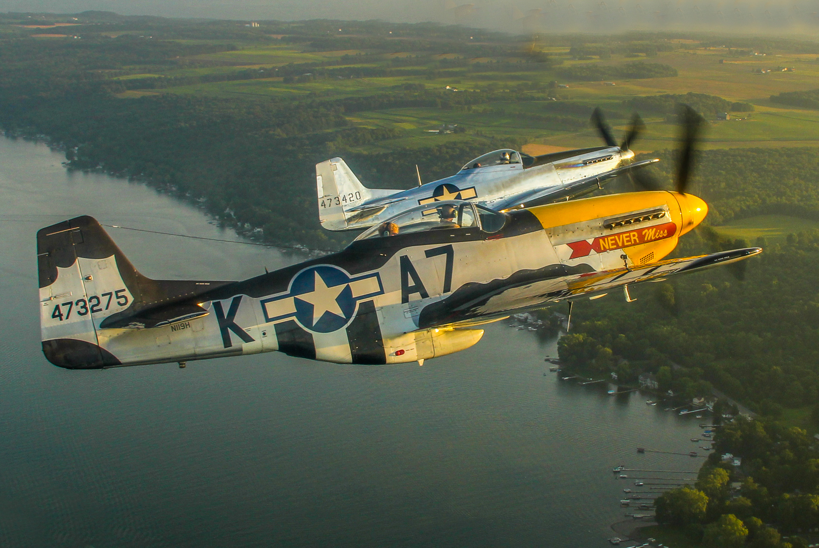 A stunning air-to-air of Mustangs over the Genesee Valley with Mark Murphy flying 'Never Miss' and Andrew McKenna in his factory-fresh P-51D. (photo by Tom Pawlesh)