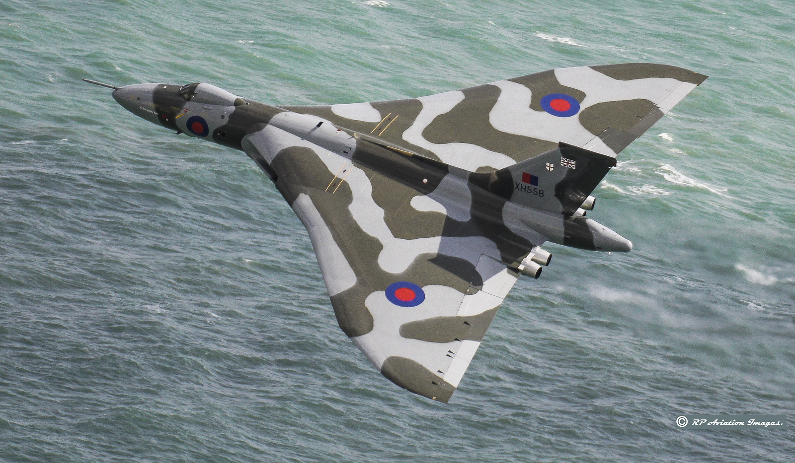 A fabulous view of XH558 as she roars over the water at Beachy Head in southern England. (photo by Robin Pettifer)