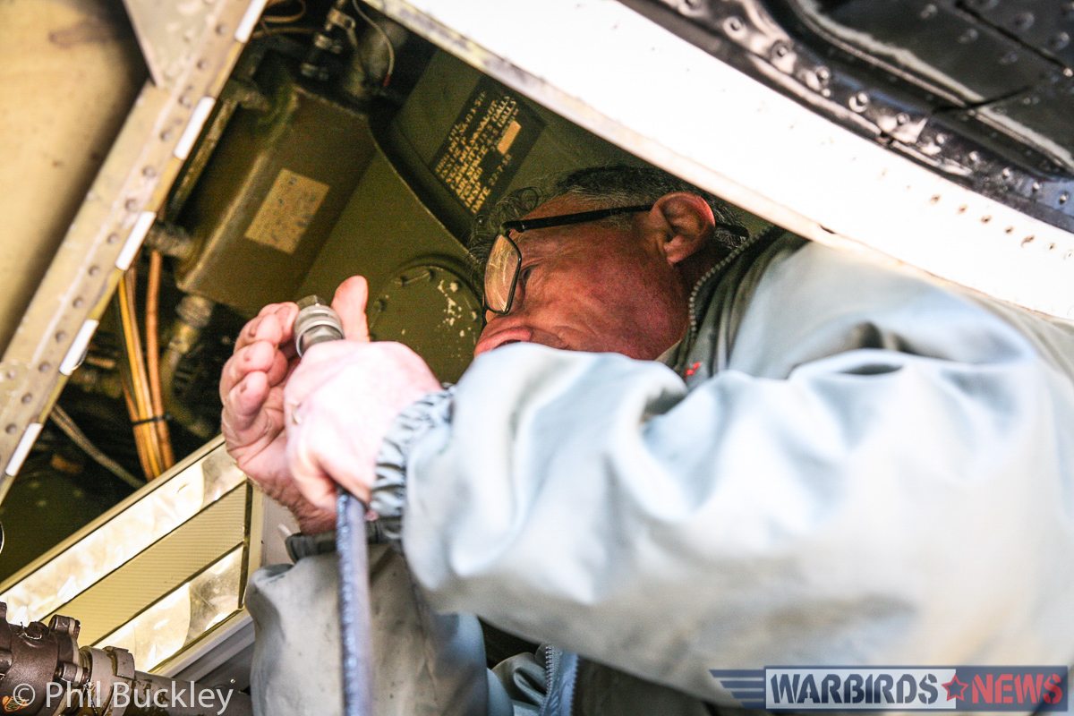 John Land working inside the engine nacelle during the brake line bleed work. (photo by Phil Buckley)