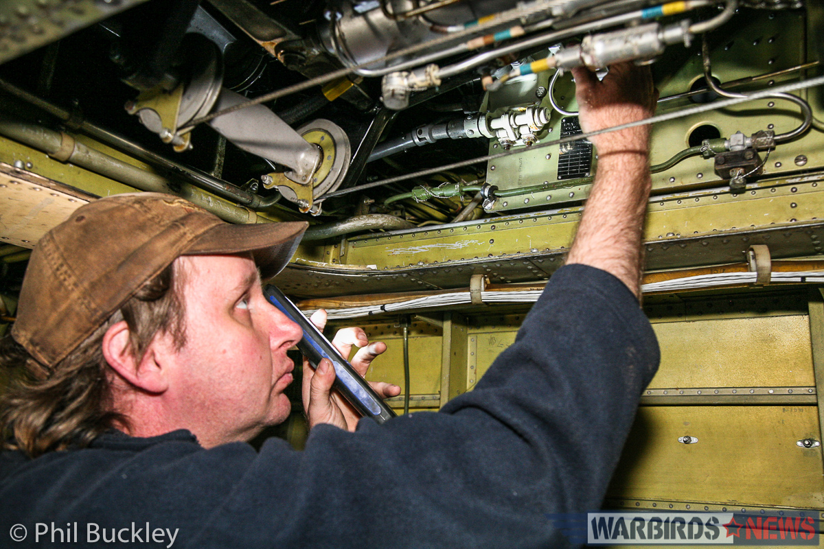 Mark Booth working inside the engine nacelle during the brake line bleed. (photo by Phil Buckley)