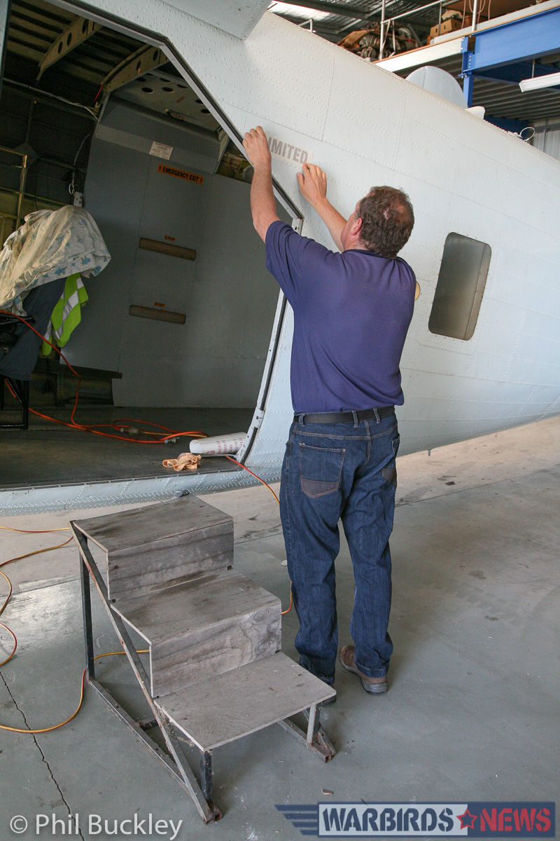 Richard Thompson applying the 'LIMITED' stencil to the fuselage near the cargo door. (photo by Phil Buckley)