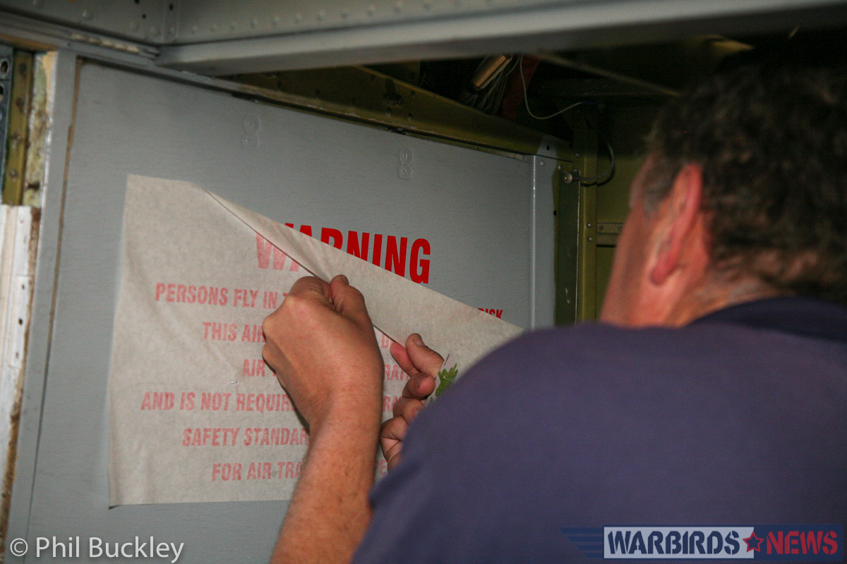 Richard Thompson applying the Warning decal inside the . (photo by Phil Buckley)
