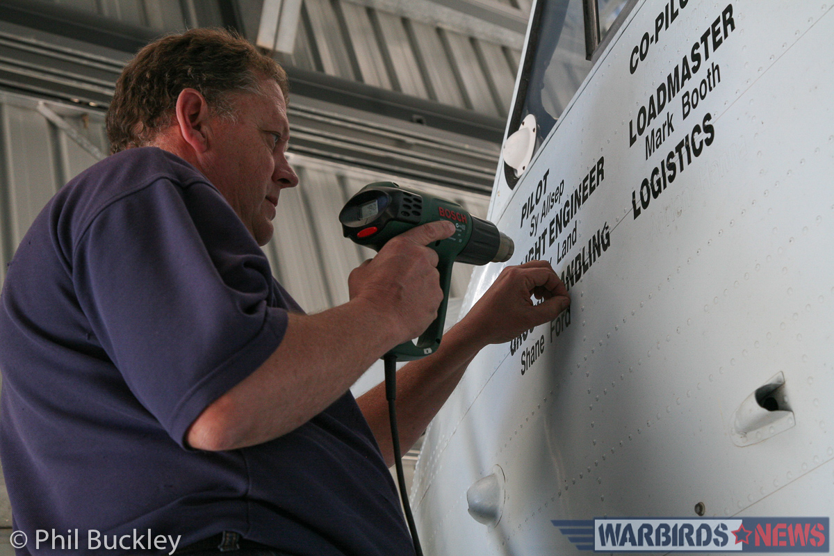 Richard Thompson using a heat gun to remove the old aircrew stenciling from the cockpit side. (photo by Phil Buckley)