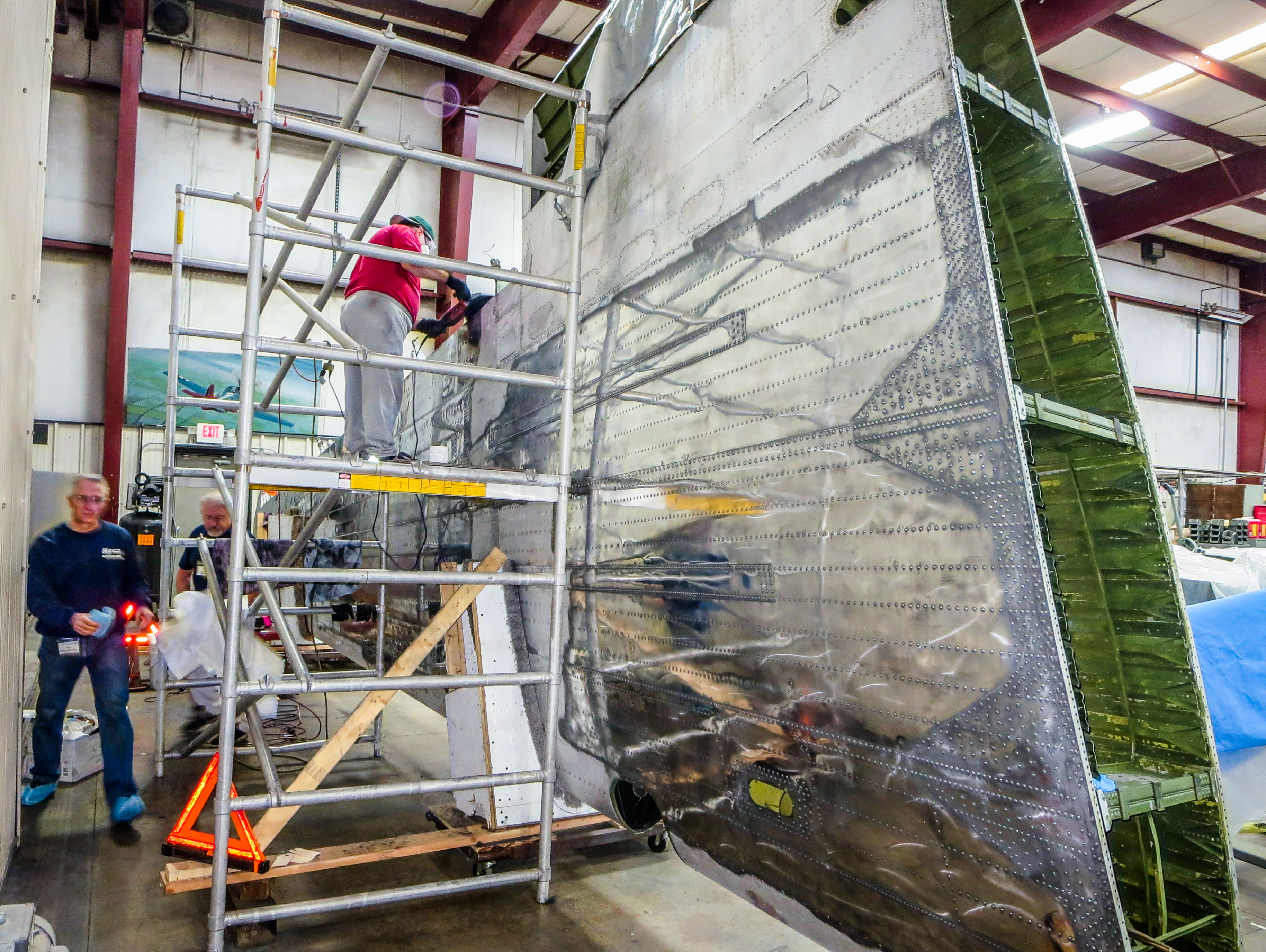Members of the restoration team soon got to work polishing the left wing. (photo via NEAM)