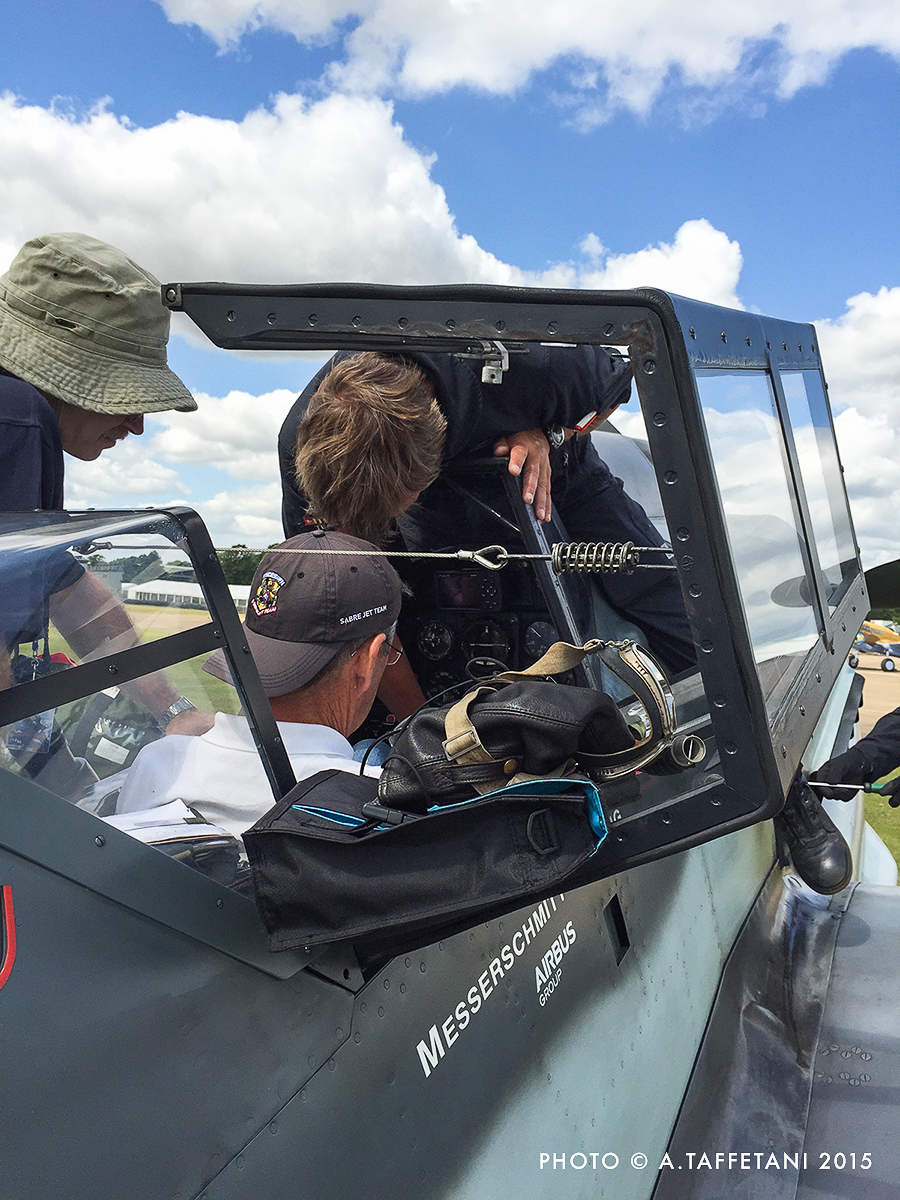 Steve Hinton sitting in the Bf 109G-4's cockpit with Klaus Plasa giving him the tour. (photo by Alessandro Taffetani)