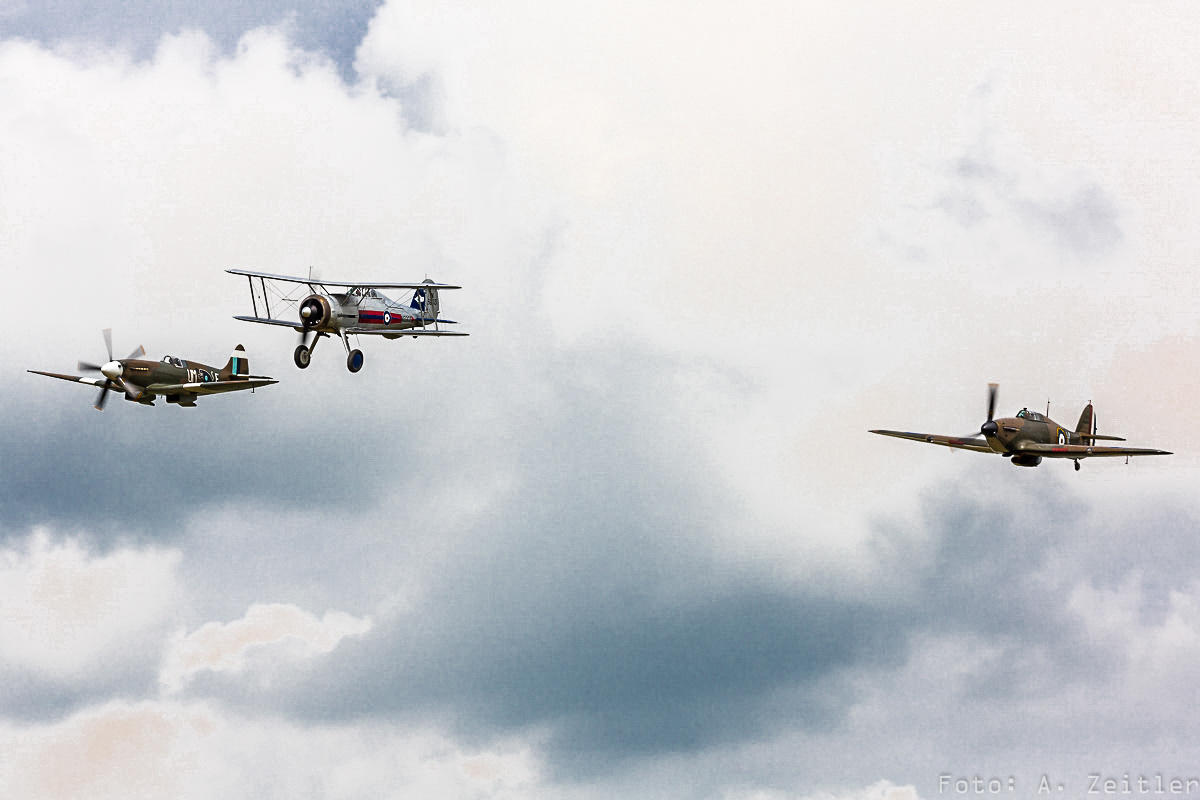 A Gloster Gladiator in formation with a Battle of France-veteran Hawker Hurricane and a Supermarine Spitfire.