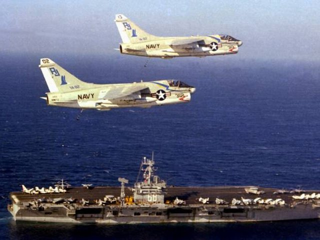 Two A7 Corsairs soar above the USS Nimitz in 1979. The top aircraft, plane 303, is on display at Edwardsville Township Community Park and will be restored with the help of the Flight Deck Veterans Group ( US NAVY Archives/A-7 Assn)