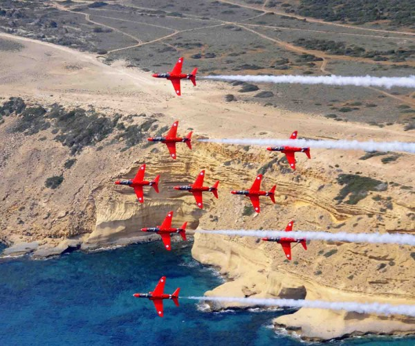 "The Royal Air Force Aerobatic Team (RAFAT) The Red Arrows are currently on detachment at RAF Akrotiri in Cyprus. During the detachment The Red Arrows are practicing their display routine three times a day in training for the Public Display Authority (PDA) on 17th May 2013, which will allow them to display to the public during the summer season. During this detachment Red 10 Sqn Ldr Mike Ling has taken the RAFAT photographers up in his jet to conduct a ""Photochase"", photographing the jets display from the air. The purpose of this Photochase was to take an image of the nine jets in their ""Lancaster"" formation, to mark the 70th anniversary of the Dambusters Raid. Image entered the photcompetition in Category D Equipment under the title Lancaster. Image shows: The nine Red Arrows jets in Lancaster formation flying above the cliff of RAF Akrotiri. Image by SAC Craig Marshall (RAF) 15 Apr 2013 Crown Copyright"