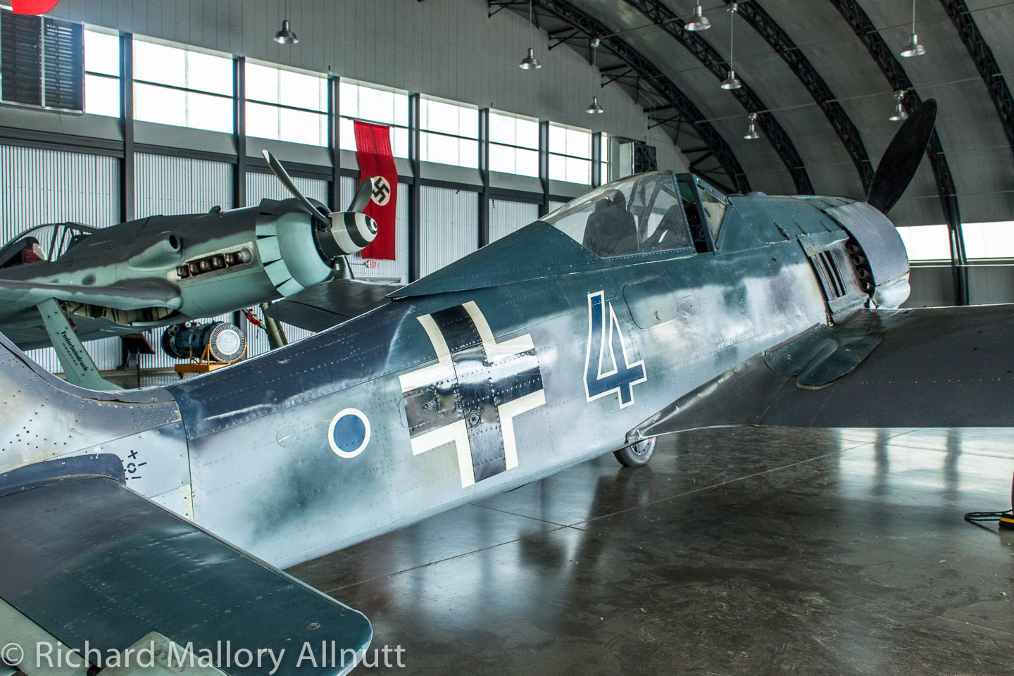 Two of Jerry Yagen's Fw-190s (an original A-model in foreground, and a replica D model in the back) sitting inside an original Luftwaffe hangar imported from Cottbus, Germany. (photo by Richard Mallory Allnutt)