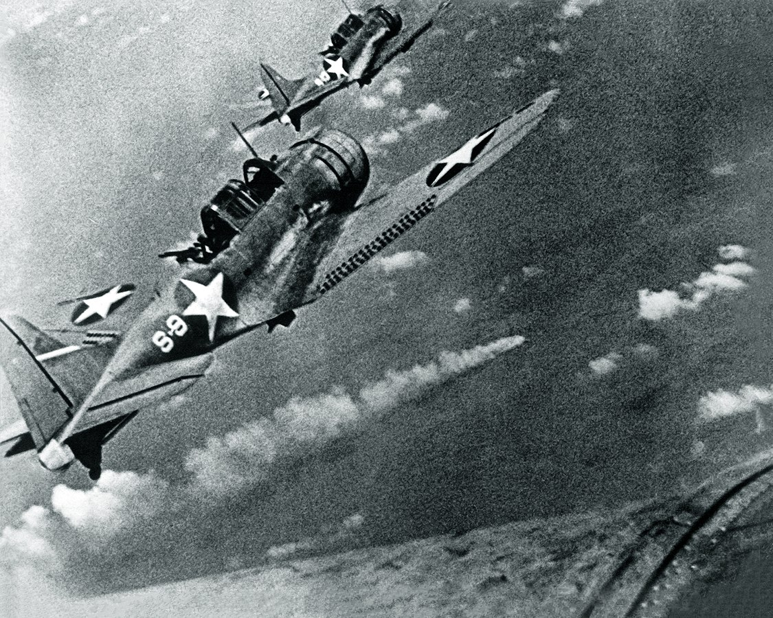 "U.S. Navy Douglas SBD-3 ""Dauntless"" dive bombers from scouting squadron VS-8 from the aircraft carrier USS Hornet (CV-8) approaching the burning Japanese heavy cruiser Mikuma to make the third set of attacks on her, during the Battle of Midway, 6 June 1942. Mikuma had been hit earlier by strikes from Hornet and USS Enterprise (CV-6), leaving her dead in the water and fatally damaged. Note bombs hung beneath the SBDs. U.S. Navy photo"