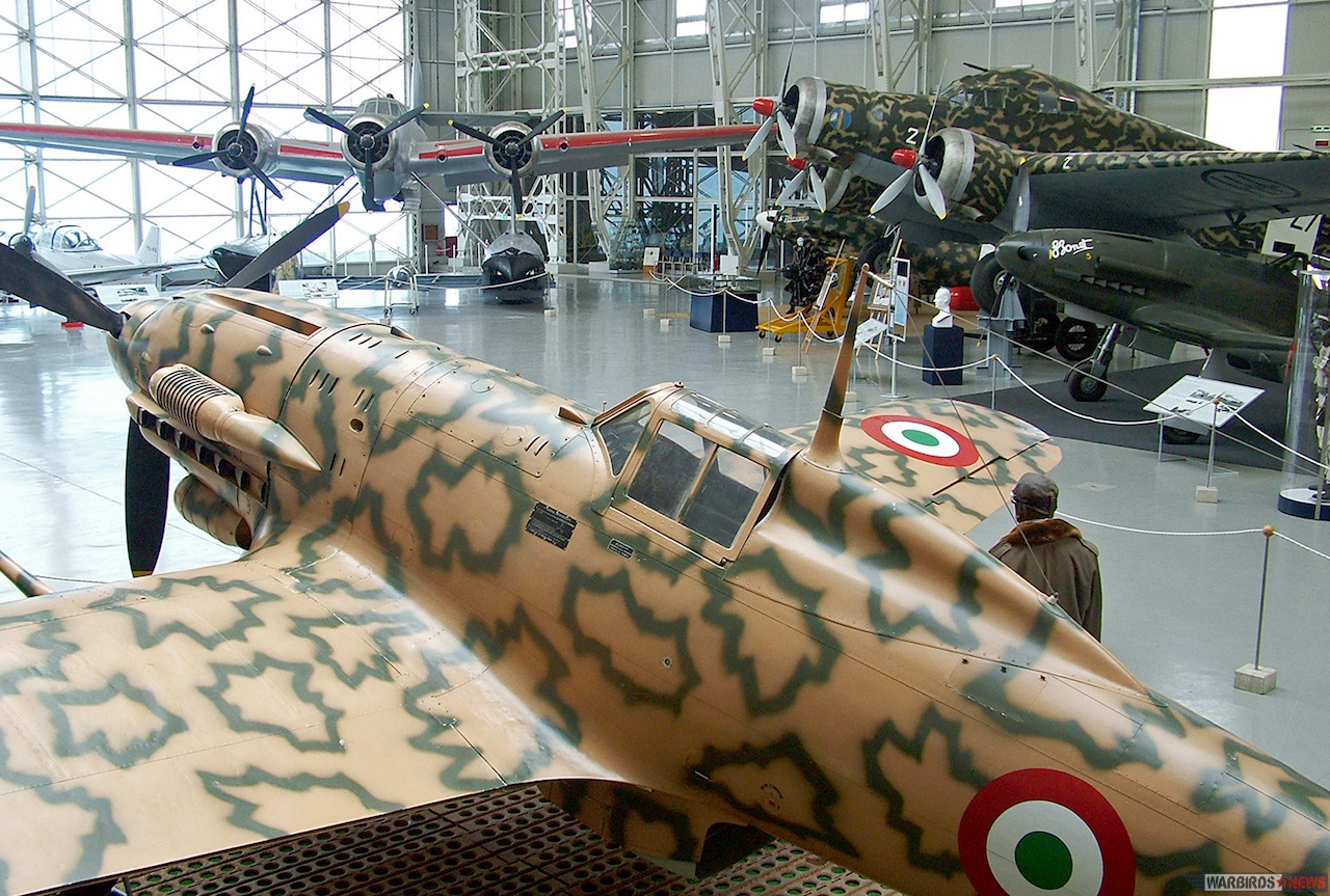 "The Badoni Hall is the third of the Museum's Halls and a classic example of a building in iron of the 1930's. the Macchi MC.205 ""Veltro"" (MM 9546) in the foreground was built by Breda in 1942, modifying a MC.202 ""X-series""; it displays the co-belligerent markings."
