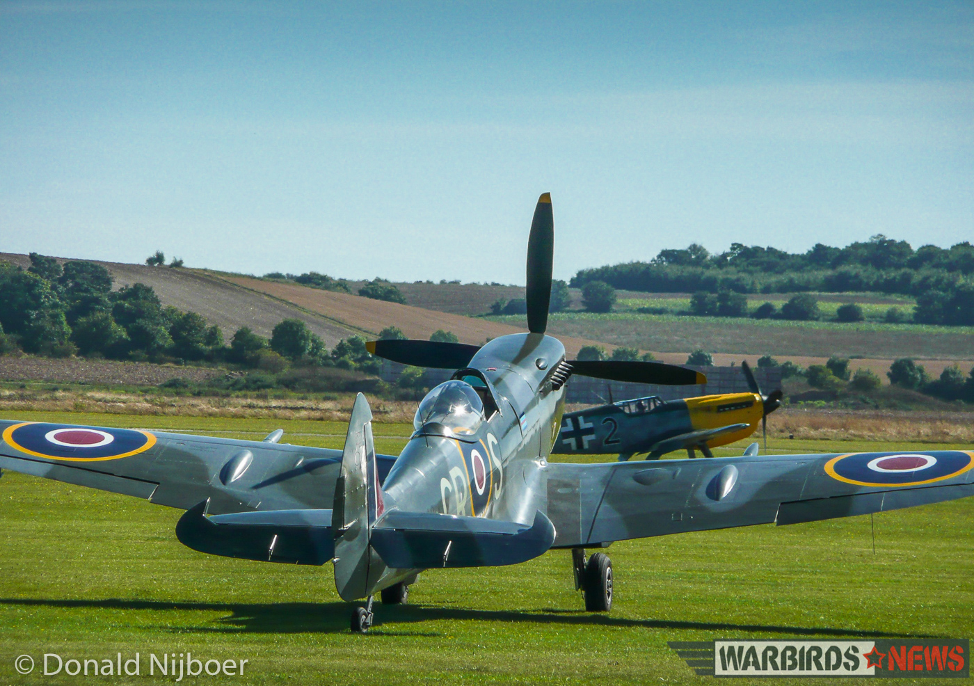 Supermarine Spitfire Mk.XVI TD248 sits on the grass at Duxford while a Hispano Buchon dummied up to represent a Messerschmitt Bf 109 taxies by in the background. (photo by Donald Nijboer)