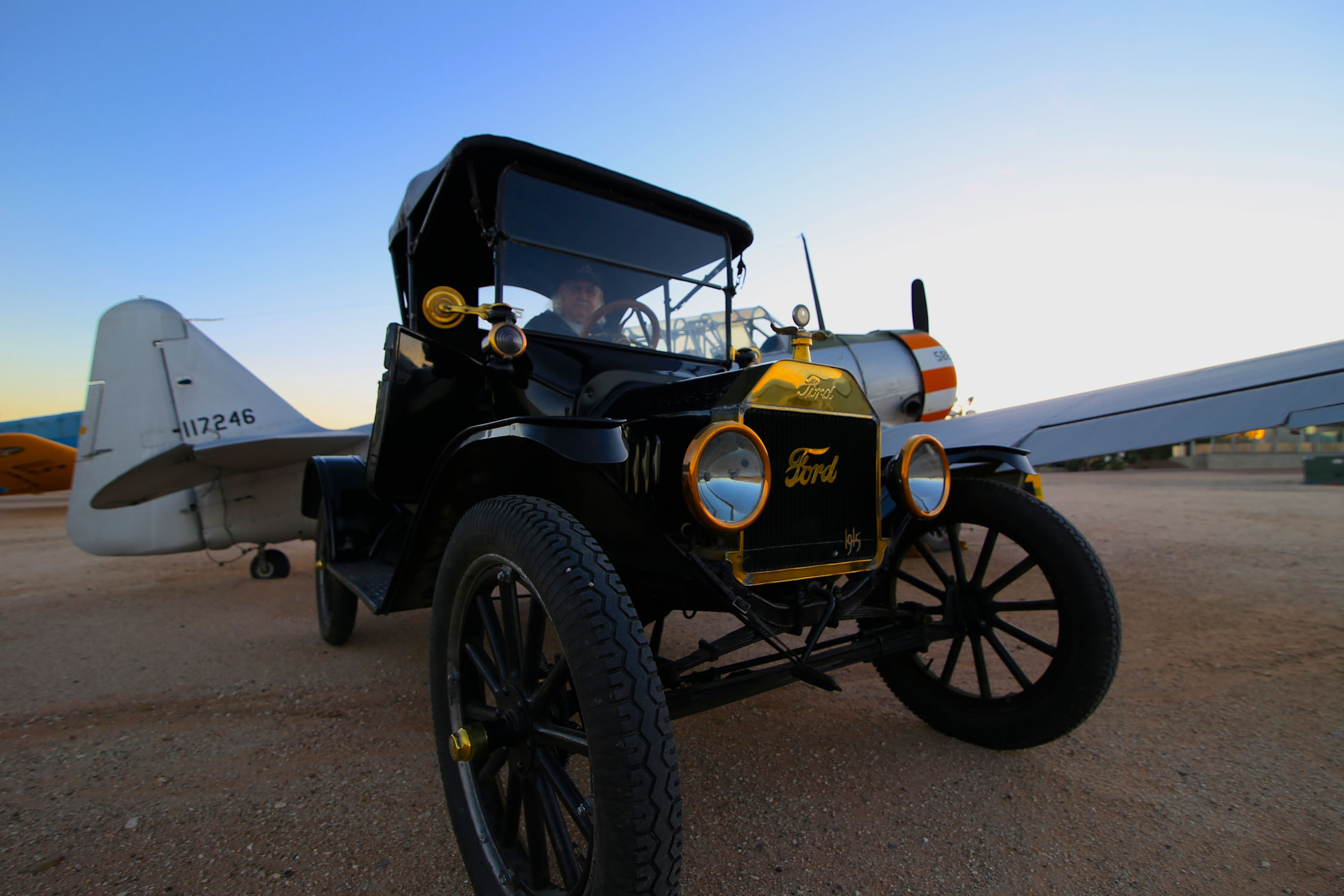 om Wulfe, Pima Air & Space Museum volunteer, Model A & T Club member, and former pilot, with his restored Model T in front of a plane style he previously flew, an AT-6 Texan. Photo by Richard Johnson.