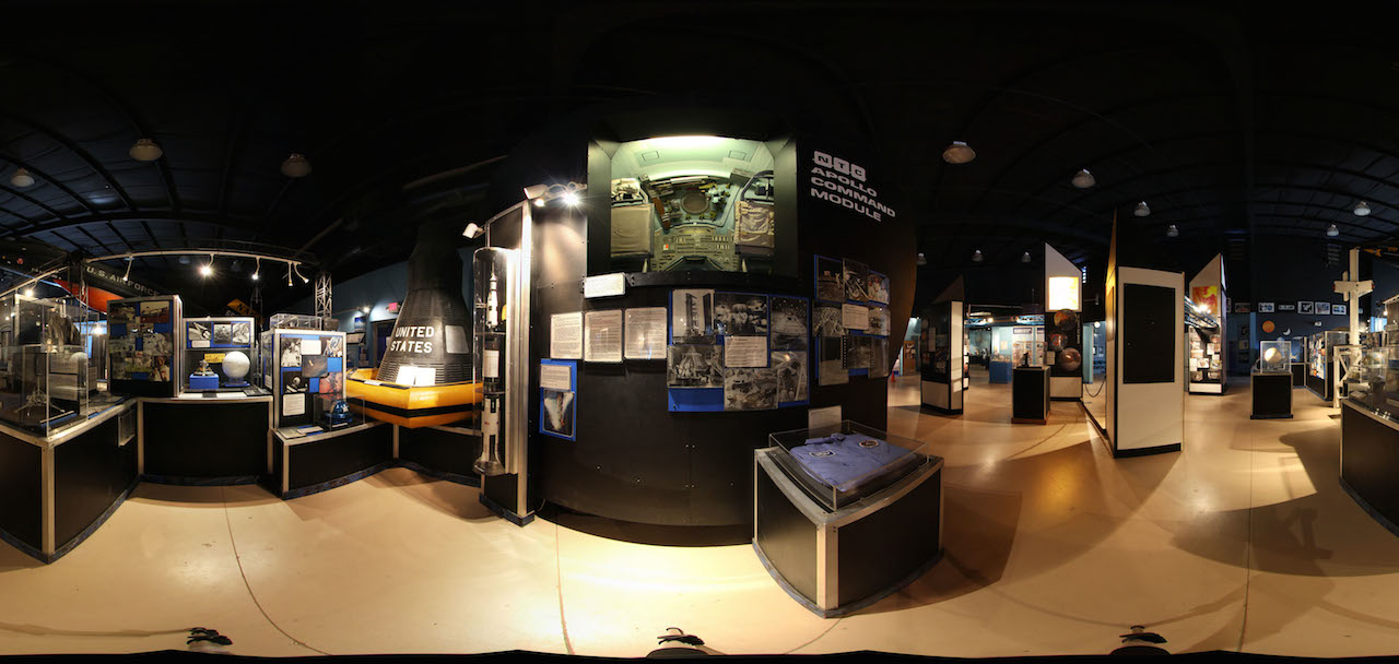 A mock-up of the Apollo 13 Command Module built for Walter Kronkite news coverage (in the greenish tinted window/box, center) and a black capsule used for rescue exercises grace other exhibits in the Space Gallery at the Pima Air & Space Museum (panoramic photo by John Saunders)