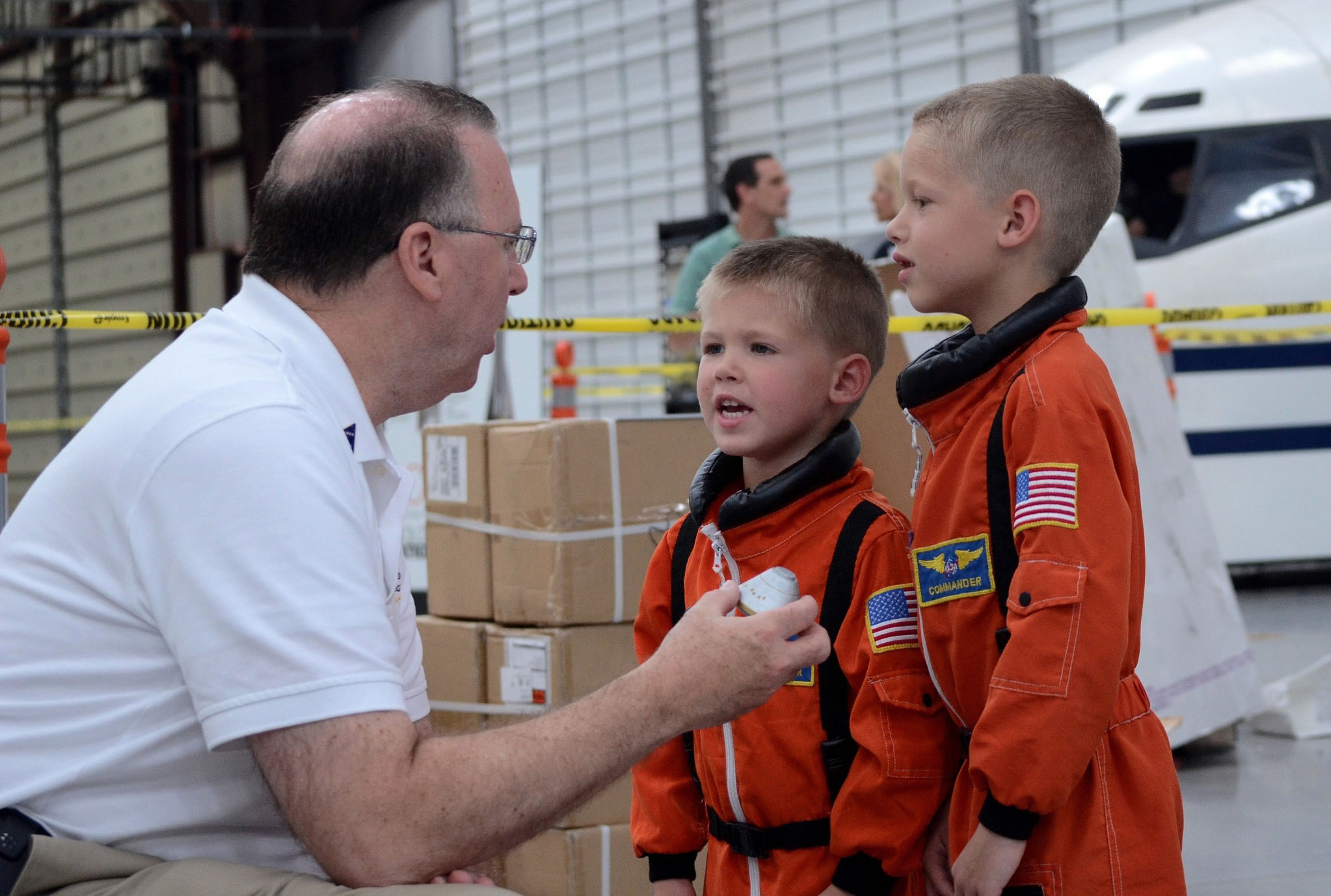 Brothers and future astornauts Galeb (4 years old) and Aiden (7 years old) Mann discuss Orion's journey with a Lockheed Martin team member. Photo by John Bezosky Jr.