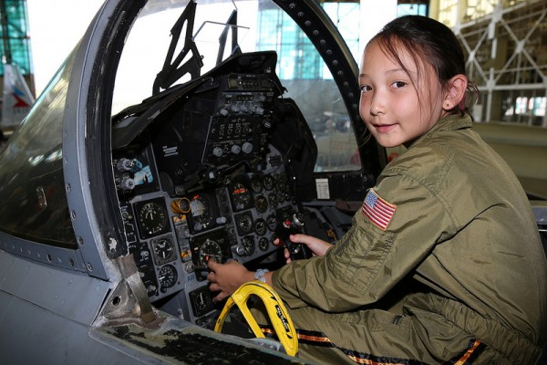 "A your girl enjoying the excitement of ""flying"" a jet.(Image credit Pacific Aviation Museum)"