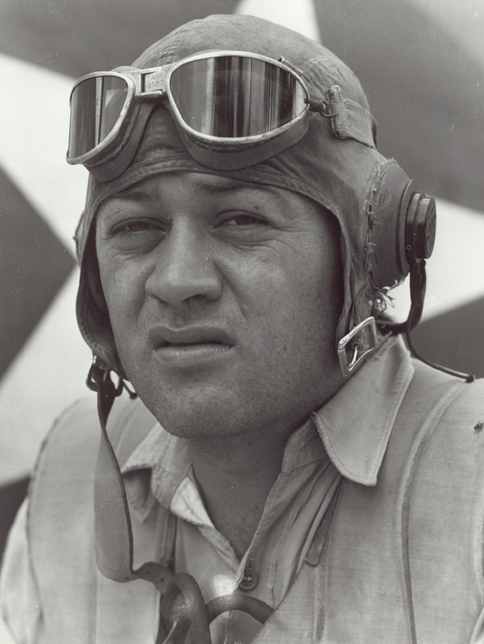 A well known publicity photo of Gregory 'Pappy' Boyington standing beside his Corsair. (photo via Wikipedia)