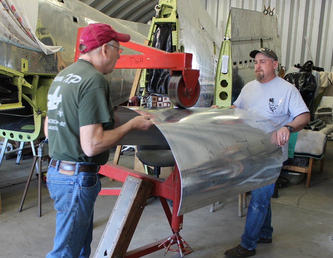 Paul and Randall hand forming the nose cowling skins using an English Wheel. (photo via Tom Reilly)