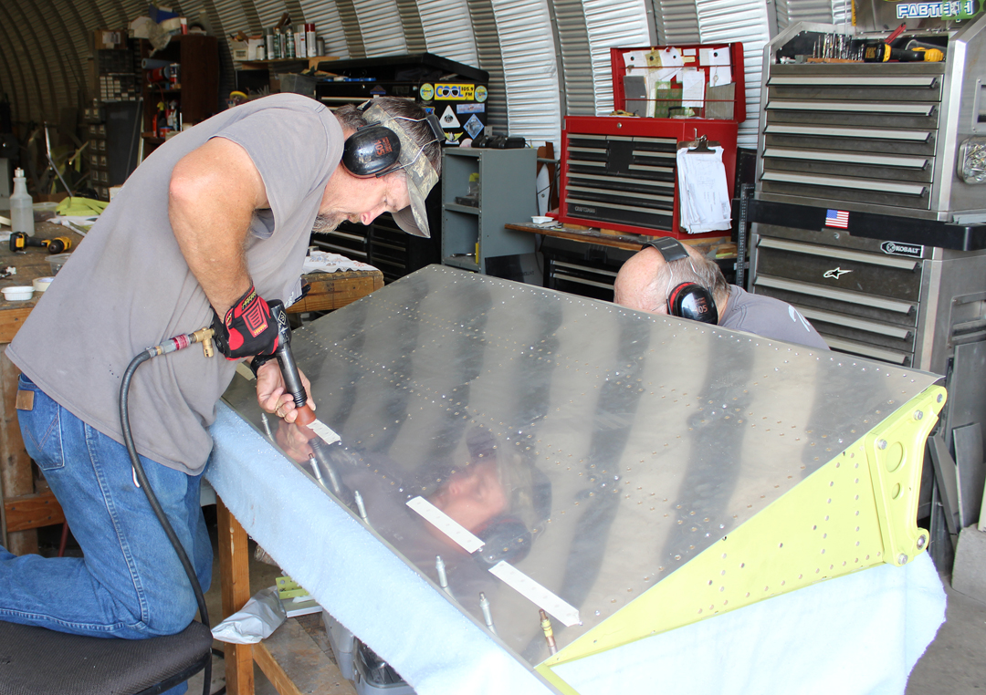 Paul and Randall riveting the outer skins to one of the flaps. (photo via Tom Reilly)