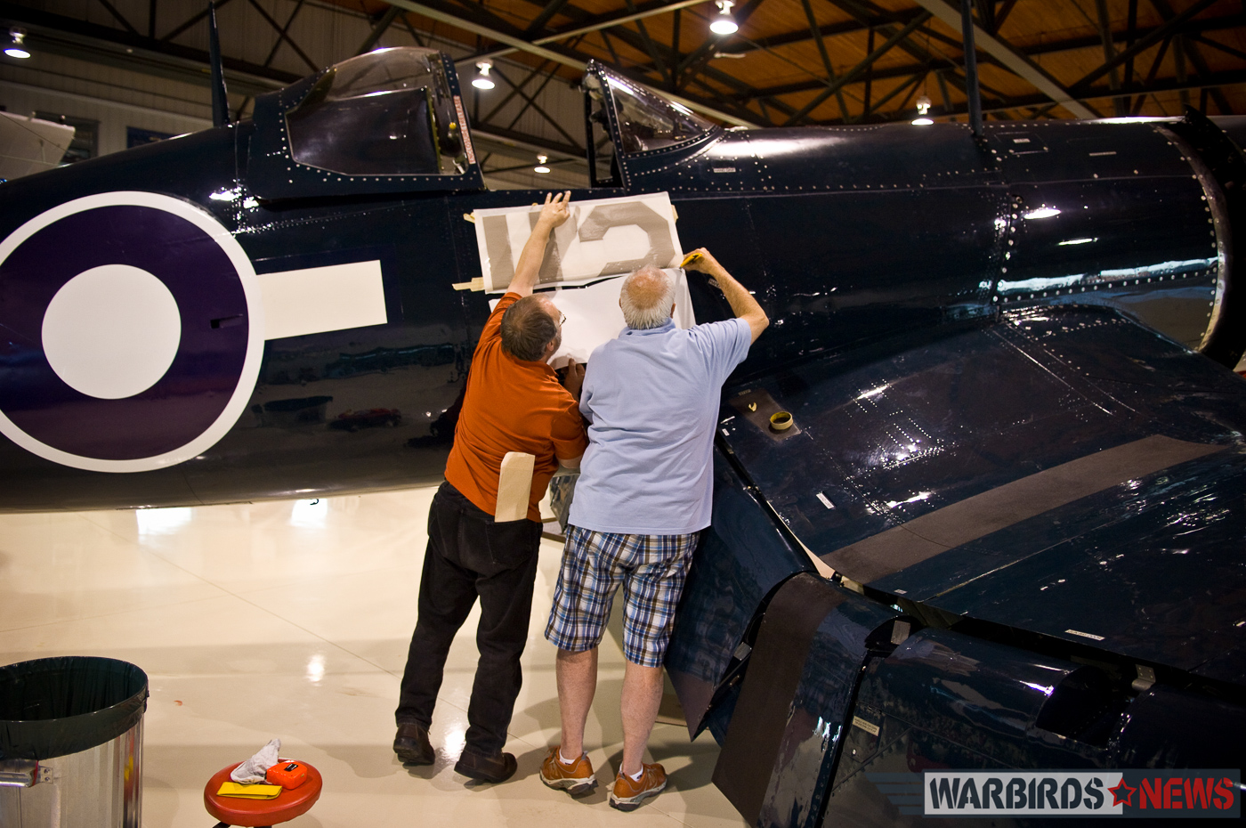 Dave O'Malley (right) and a colleague applying the decals to transform FG-1D Bu.92106 into Robert Hampton Gray's Corsair IV. (photo by Peter Handley)
