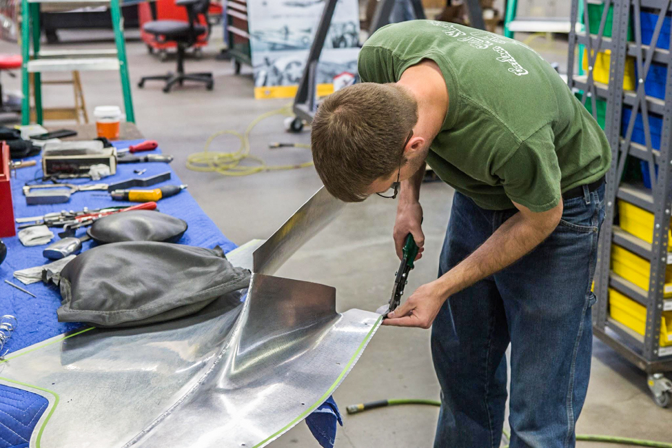 Randy carefully trims a fillet piece that smooths the wing trailing edge to fuselage juncture. (photo via AirCorps Aviation)