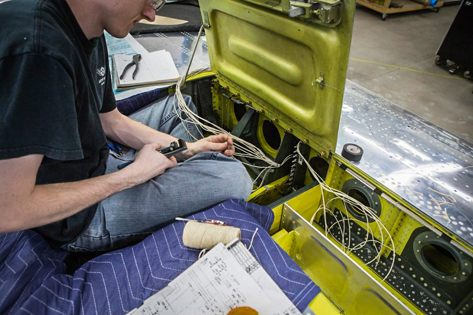 Aaron works to connect the various harnesses to the terminal strip visible ahead of his knee. (photo via AirCorps Aviation)