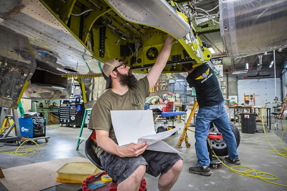 Randy checks the engineering drawings as he looks over gear well installations. (photo via AirCorps Aviation)