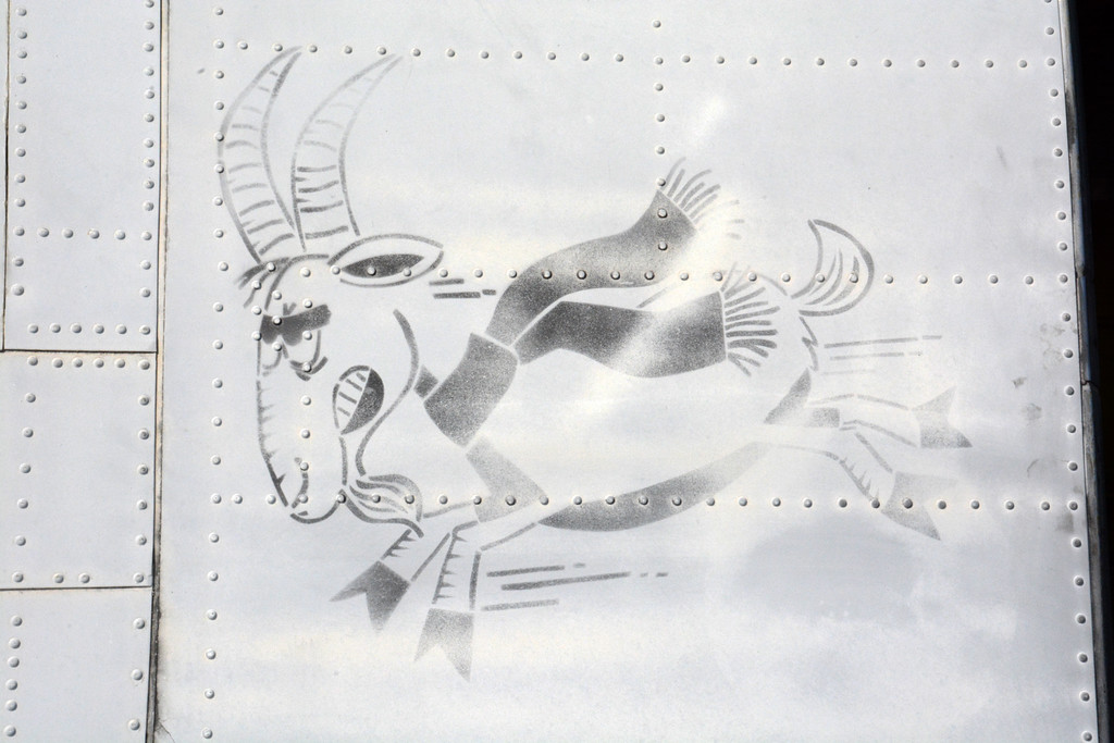 """The unusual """"bucking goat"""" motif stenciled upon RU21A 67-18113's fuselage, as seen when the aircraft was in Dynamic Aviation's storage compound. This will be faithfully re-applied to the airframe after the new paint goes on. (photo by Bryan Miklos)"""