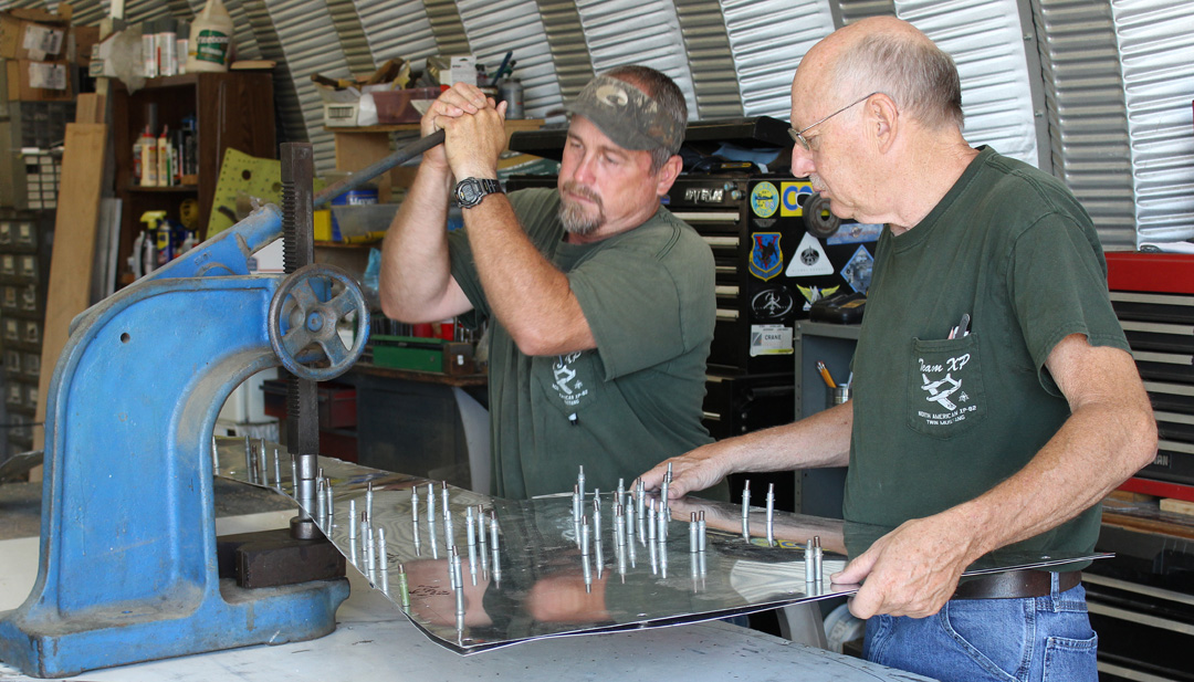 Randall & Paul press-dimpling the cowling side skins for the Dzus fasteners. (photo via Tom Reilly)