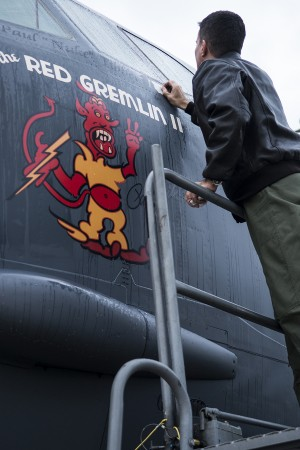"U.S. Air Force Capt. Kerry Baker applies nose art on a 93rd Bomb Squadron B-52H Stratofortress, Nov. 15, 2013, Barksdale Air Force Base, La. The original ""Red Gremlin"" nose art was on a World War II B-17 bomber piloted by Brig. Gen. Paul Tibbets, Jr. (U.S. Air Force photo by Master Sgt. Greg Steele/Released)"