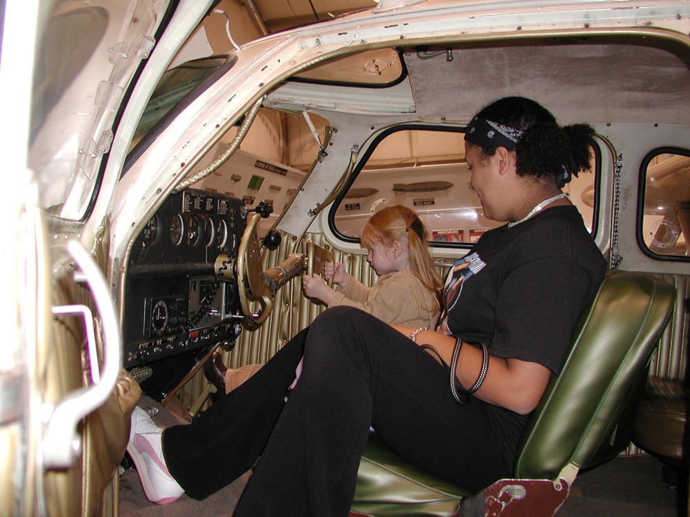 A young woman introduces her daughter to the cockpit of the NEAM Republic Seabee. Under careful supervision, this is a marvelous way to introduce a child to the life-long adventure aviation can provide. (photo via NEAM)