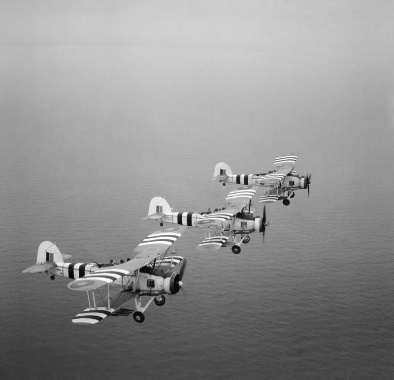 Rocket-armed Fairey Swordfish on a training flight from RNAS St Merryn in Cornwall, 1 August 1944. Three rocket projectile Fairey Swordfish during a training flight from St Merryn Royal Naval Air Station This operational squadron was commanded by Lieutenant Commander P Snow RN. Note the invasion stripes carried for the Normandy landings on the wings and fuselage of the aircraft.