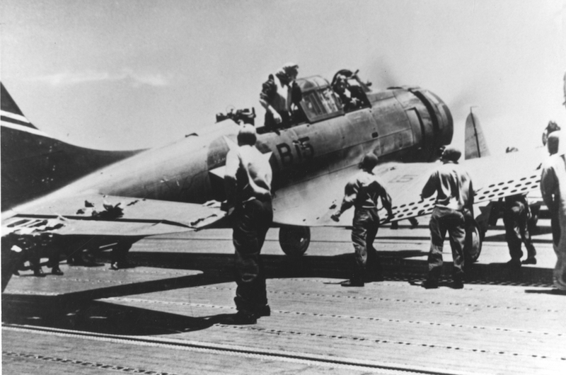 "A U.S. Navy Douglas SBD-3 ""Dauntless"" scout bomber (BuNo 4542), of Bombing Squadron Six (VB-6) from USS Enterprise (CV-6), after landing on USS Yorktown (CV-5) at about 1140 hrs on 4 June 1942, during the Battle of Midway. This plane, damaged during the attack on the Japanese aircraft carrier Kaga that morning, landed on Yorktown as it was low on fuel. It was later lost with the carrier. Its crew, Ensign George H. Goldsmith, pilot, and Radioman 1st Class James W. Patterson, Jr., are still in the cockpit. Note damage to the horizontal tail."