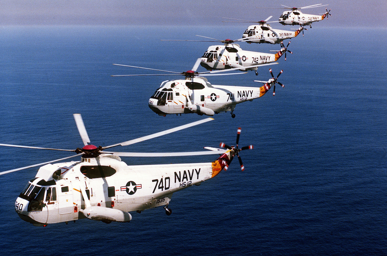 "Five U.S. Navy Sikorsky SH-3H Sea King anti-submarine warfare helicopters from Helicopter Anti-Submarine Squadron HS-12 ""Wyverns"" flying in formation, in 1985. HS-12 was assigned to Carrier Air Wing 5 (CVW-5) aboard the aircraft carrier USS Midway (CV-41). ( Image credit US NAVY via Wikipedia)"
