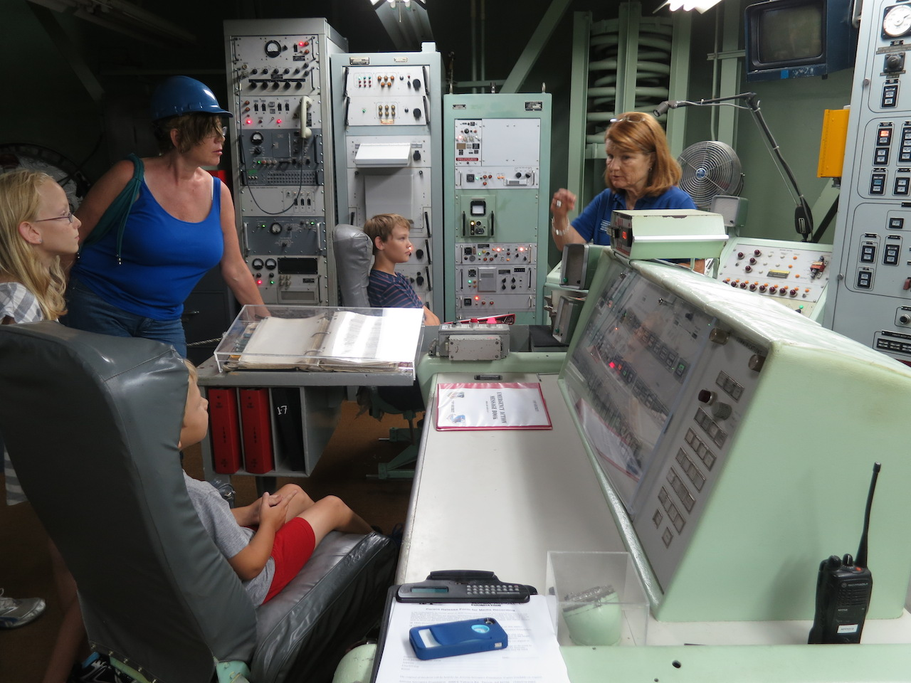 A family experiencing the Titan Launch Control Center tour with docent and past crew member Maggie.