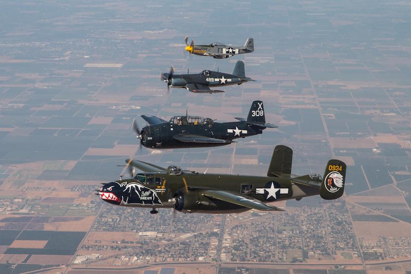From bottom to top: A B-25J Mitchell bomber, TBM-3E Avenger torpedo bomber, FG-1D Corsair fighter, and P-51D Mustang fighter flown by the Texas Flying Legends are escorted into Edwards AFB airspace by a C-12 crew from the 419th Flight Test Squadron Sept. 18. (U.S. Air Force photo by Donald R. Allen)