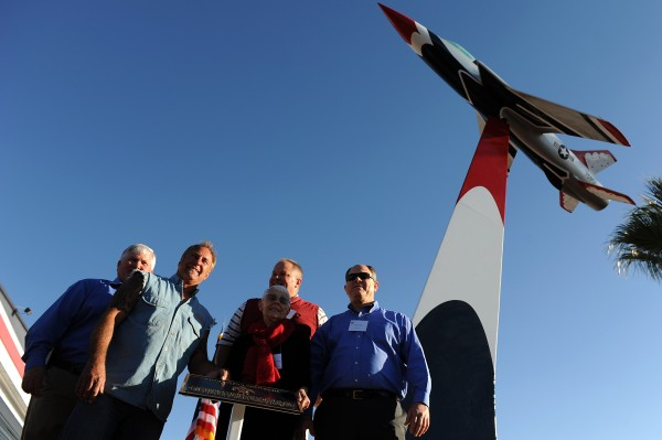 "From left: Bill Devlin, Rick Dale, Mark Devlin, Shirley Buckley, and Bill Devlin. Buckley and her sons were the guests of honor at a ceremony Nov. 15, 2013, to dedicate an F-105 ""Thunderchief"" replica in front of the Thunderbirds hangar. Buckley's late husband, Capt. Gene Devlin, was killed in an F-105 accident in 1964, and the 39-year-old memorial display was recently reconditioned at ""Rick's Restorations"" in Las Vegas. (U.S. Air Force photo/Staff Sgt. Larry E. Reid Jr.)"